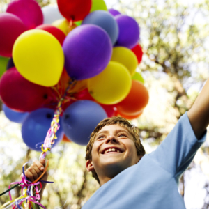 Young Boy Holding a String of Balloons --- Image by © Royalty-Free/Corbis